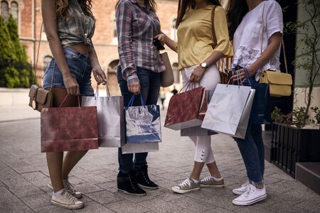 Women in shopping. Happy girls with shopping bags enjoying in shopping. Consumerism, shopping, lifestyle concept