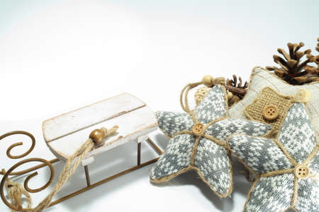 Christmas greeting card or backround decoration in vintage classic style. Decorations are cotton stars, sledge and pine cones.