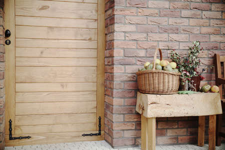 Brick wall and sliding wooden door in vintage style and old Victorian England style, with decorations, autumn berries and wicker basket. Captured on a sunny day