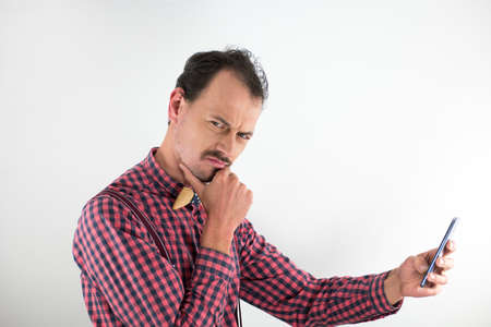 Portrait of caucasian man in middle age, thirty years old. Wearing shirt and wooden bowtie. Studio photo with white background. Holding mobile phone in the hand and he makes gesture Stock Photo