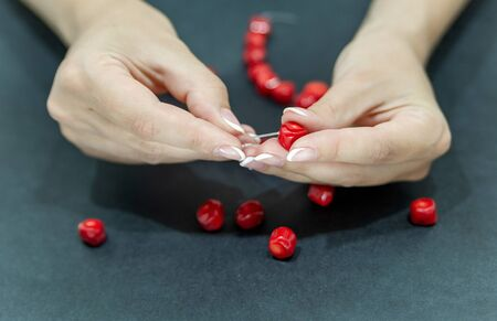 Close-up of hand of needlewoman making necklace of natural coral