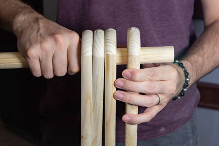 working with wood at home, man inserts wooden boards with a hole on a round stick, hobby
