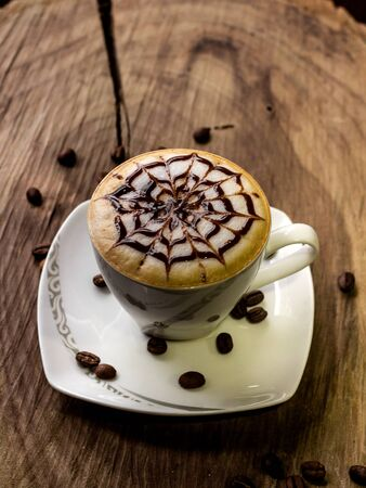 coffee cup latte art made with organic coffee, chocolate and coffee beans on background and on wooden background