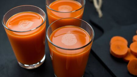 Freshly prepared carrot juice, chopped vegetable lying next to it.