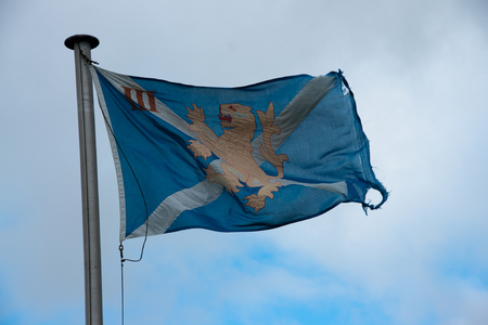 Scottish military flag in the wind with cloudy sky Stock Photo