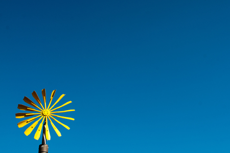 Yellow wind wheel with a blue cloudless sky