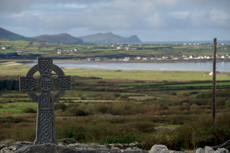 Celtic cross with irish landscape and cloudy sky