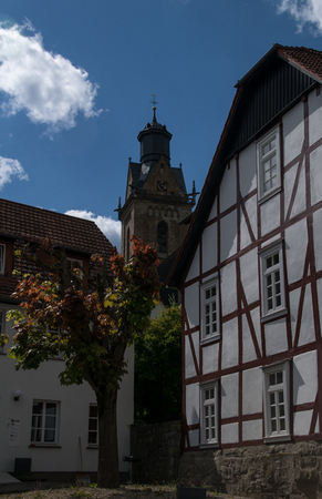 Half timbered house with the tower of the Saint Kilian church in Korbach Stock Photo