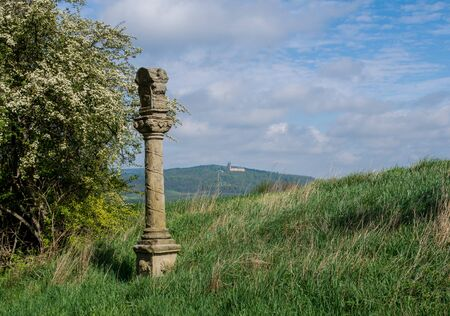 Wayside cross with cloudy sky and in the background cloister Banz
