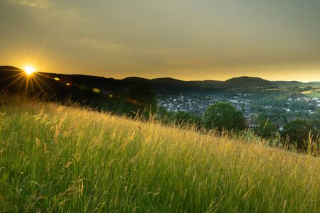 German city Hallenberg at sunset with sun flares in summer time