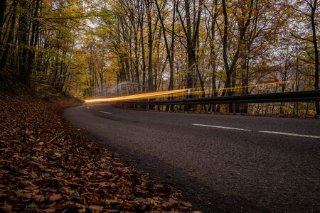 Car lightning with street in autumn in germany