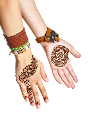 tatoo: Mehendi or henna tatoo on the female hands in bracelets isolated on white Stock Photo