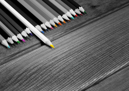distinctive: Black and white image of colored pencils with isolated pencil against a dark wooden table. The concept of personality, distinctive character