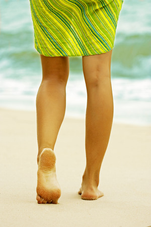 remain: Woman walking on the beach. On the sand footprints remain. Heel close up. Stock Photo