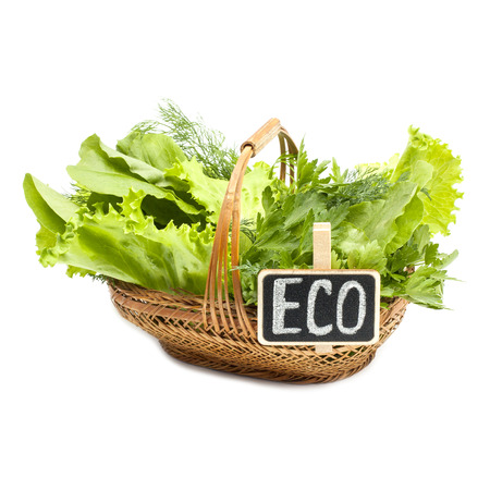 bundle of letters: Herbs in a braided wooden basket on white background with the inscription eco
