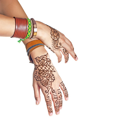 tatoo: Mehendi or henna tatoo on the female hands in bracelets isolated on white Stock Photo