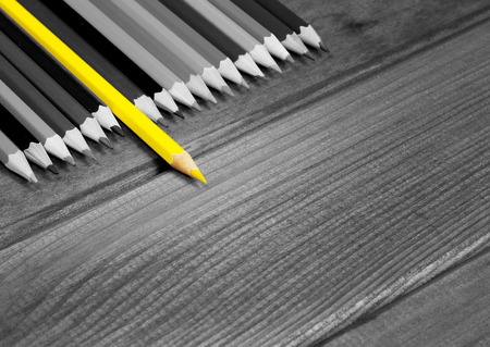 Black and white image of colored pencils with isolated yellow pencil against a dark wooden table. The concept of leadership, business, Chief