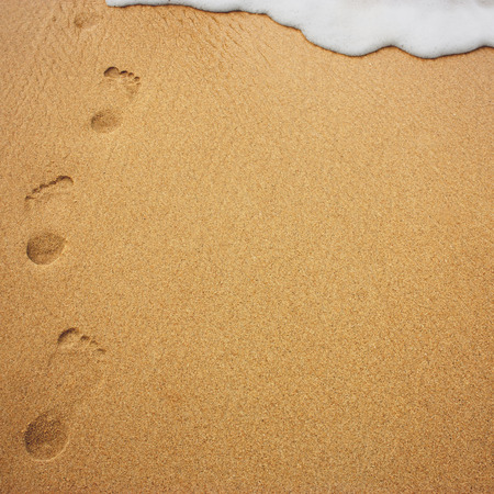 footprint sand: Human footprints in the sand disappearing under a sea wave