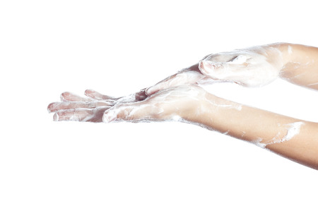 Woman washes her hands. pictured female hands in soapsuds. Isolated on white