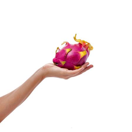 exotic fruit: Female hand holds ripe dragon fruit on white background