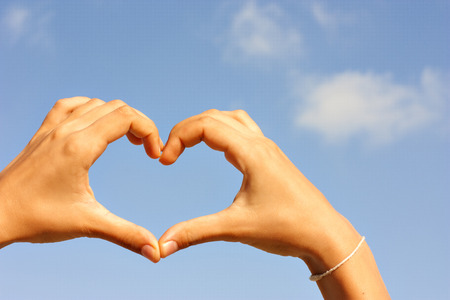 depict: Beautiful female palms depict heart on a background of blue sky with clouds Stock Photo