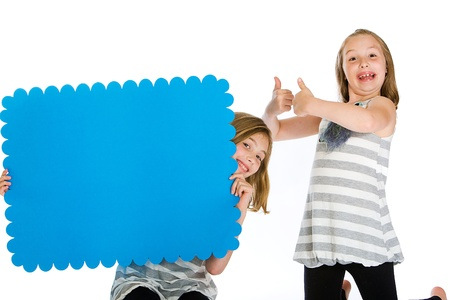 niños sosteniendo un cartel: Dos niños sosteniendo un cartel en blanco Foto de archivo
