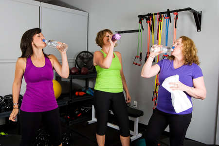 woman working out: Women drinking after a workout Stock Photo