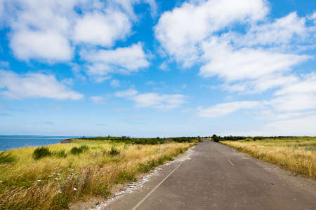 mooie landweg onder een heldere blauwe hemel Stockfoto