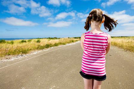 kind overweegt haar toekomst kijken onderaan een lange weg te gaan