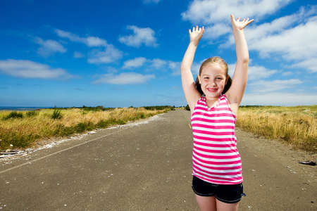 lost child: Happy young girl with her arms raised on an empty street.