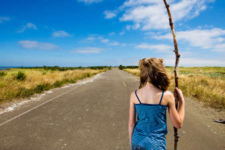 Child wandering alone on an empty road Stockfoto