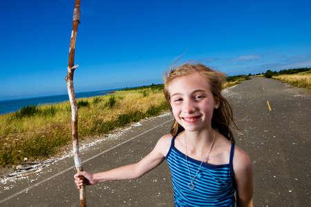 smirk: Child wandering alone on an empty road Stock Photo