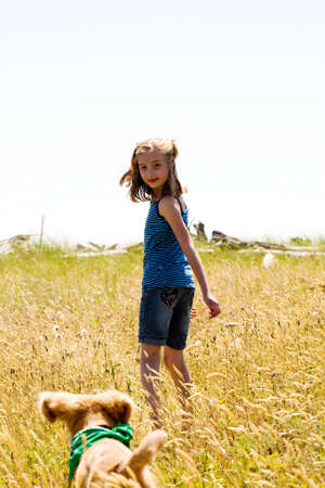 child playing with dog outside in a field photo