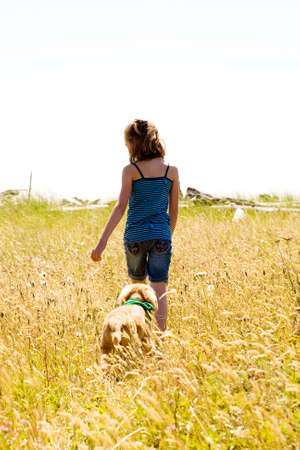 child walking a dog in a field of tall grass photo