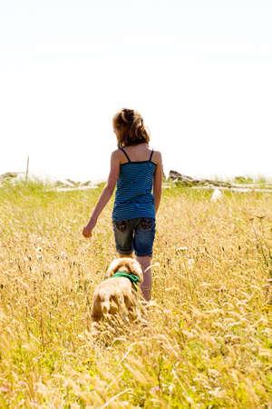 kind het lopen van een hond in een veld van hoog gras