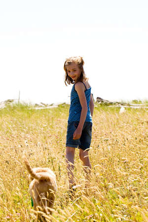 Young girl looks back at her dog in a meadow photo