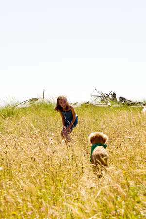 child playing with her dog in a field of tall grass photo