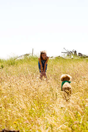 girl calling her dog while playing in a field photo