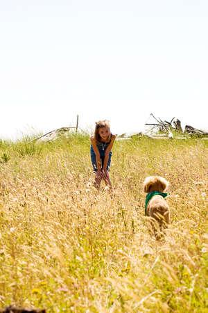 meisje roepen haar hond tijdens het spelen in een veld