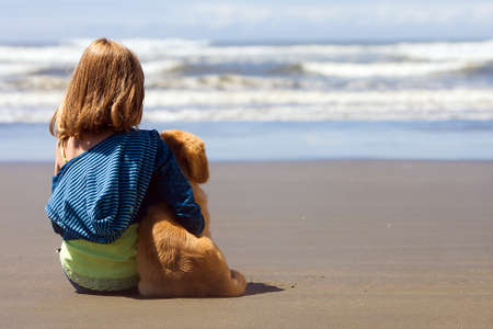 friendship: Child with her dog at the beach