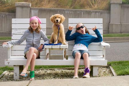 Kids Chillen zitten op een bankje in het park Stockfoto