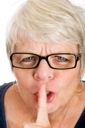 stern old woman shushing with her finger Imagens