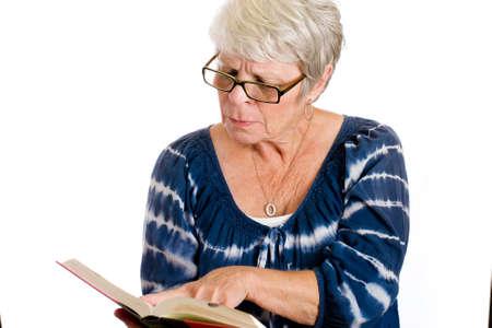 rijpe vrouw het lezen van een boek door een bril