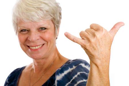 Oudere vrouw die hang loose teken