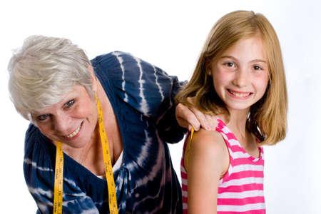 mature woman seamstress measuring child photo