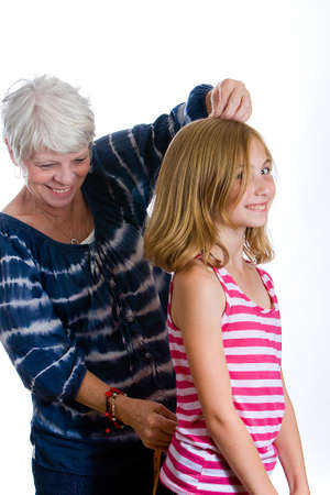 mature woman measuring child for clothes photo