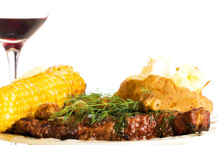 Steak dinner with a baked potato, corn on the cob and a glass of red wine photo