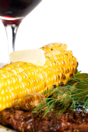 Steak dinner with corn and a glass of red wine photo