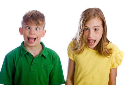 sacar la lengua: Un chico divertido y una ni�a con los ojos cruzados Foto de archivo