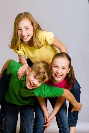 Group of young kids in colorful shirts having fun Фото со стока